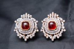Silberne handgemachte Ohrringe mit rotem Rubin und dem Gold umrissen Stockfotografie