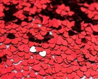 2 silberne Herzen in einem Meer des Rotes eine Stockbild