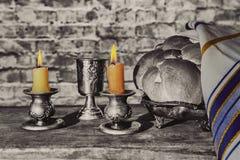Silberne kiddush Schale, Kristallkerzenständer mit brennenden Kerzen und Challah Stockfotografie