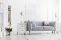 Silberne Lampen über weißen Kabinetten im Wohnungsinnenraum mit Blumen und grauem Sofa Reales Foto stockfotos