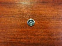 Silberne Linsentürweichzeichnung in der Mitte der braunen Holztür stockfoto