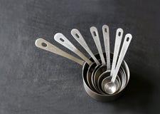 Silberne messende Schalen gestapelt auf schwarzem Hintergrund Lizenzfreie Stockfotos