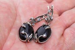 Silberne Ohrringe mit schwarzem Achat auf der Palme Lizenzfreie Stockbilder