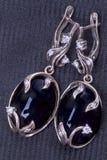 Silberne Ohrringe mit schwarzem Achat auf Gewebe Stockbilder