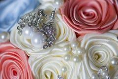 Silberne Perlenohrringe auf den Blumen gemacht von den Bändern Stockfotos