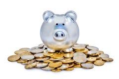 Silberne Piggy Querneigung und Münzen Stockfoto