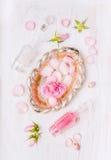 Silberne Schüssel mit Rosen im Wasser, Flasche und Knospen und Blumenblätter von Rosen auf weißem hölzernem Lizenzfreie Stockfotografie