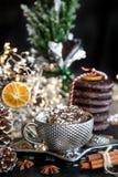 Silberne Schale der Weihnachtskarte süße Creme auf schwarzer Tabelle, mit Bonbons, Zimt, Anissamen, Winterkegel und leerem Glas lizenzfreie stockfotos