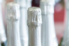 Silberne Sektflaschehälse und Spitzenkappen auf dem Stand den hellen Hintergrund im Spirituosenladen Lizenzfreies Stockbild