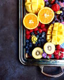 Silberne Servierplatte mit Mischung von exotischen Zitrusfrüchten des Schnittes mögen Draufsicht der Orangen, der Mango, der Kiwi Stockfotos