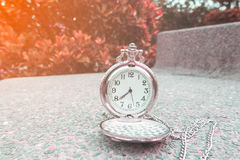 Silberne Taschenuhr auf einem Steinstuhl Stockfotografie