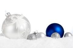 Silberne und blaue Verzierungen im Schnee Stockfotos