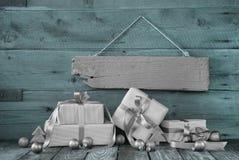 Silberne Weihnachtsgeschenke auf hölzernem Hintergrund mit einem Zeichen Stockbilder