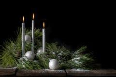 Silberne Weihnachtskerzen mit Immergrün und Schnee Lizenzfreie Stockfotografie