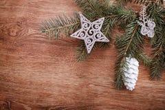 Silberne Weihnachtsverzierungen und Tannenbaumast auf einem rustikalen hölzernen Hintergrund Abbildung innen Glückliches neues Ja Lizenzfreie Stockfotos