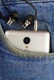 Silberner Aluminiumsmartphone mit Kopfhörer in der Tasche Blue Jeans Lizenzfreie Stockbilder