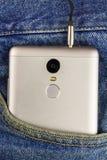 Silberner Aluminiumsmartphone mit Kopfhörerkabel in der Tasche Blue Jeans Stockfotografie