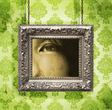 Silberner Bilderrahmen gehangen gegen Blumentapete Lizenzfreie Stockfotos