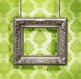 Silberner Bilderrahmen gehangen gegen Blumentapete Stockfoto
