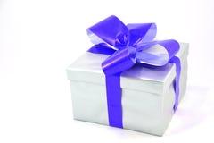 Silberner Geschenkkasten mit dem blauen Bogen getrennt auf Weiß Lizenzfreies Stockfoto