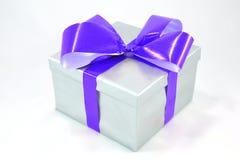 Silberner Geschenkkasten mit dem blauen Bogen getrennt auf Weiß Stockfotos