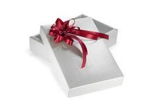 Silberner Geschenkkasten mit rotem Farbband Stockbilder