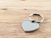 Silberner Herz-Schlüsselanhänger auf Holz Lizenzfreie Stockfotografie