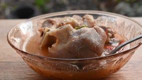 Silberner Löffel, der würziges gekochtes Schweinefleischbein in Tom Yum-Suppe auf Schüssel schaufelt stock video footage