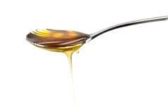 Silberner Löffel mit goldenem Honig Stockbilder