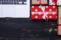 Silberner Laptop auf einem Hintergrund mit einem viel der bunten Geschenkbox Lizenzfreies Stockbild