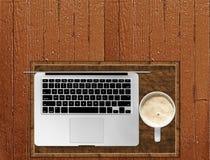 Silberner Laptop und Kaffee auf Tabelle Browns hölzernem Copyspace-Blog Stockbild