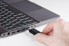 Silberner Laptop und Mann übergeben das Halten von USB grelle Scheibe und die Verstopfung Stockfotografie