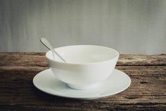 Silberner Löffel in der weißen Schüssel und in der weißen Platte auf hölzerner Tischplatte Stockfotos