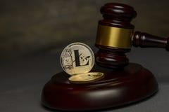 Silberner litecoin Stand mit Richterhammer auf dunklem Hintergrund stockfoto