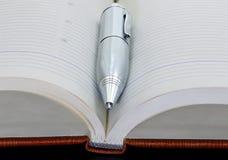 Silberner Metallstift auf dem geöffneten Notizbuch Nahaufnahme Lizenzfreie Stockbilder