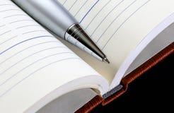 Silberner Metallstift auf dem geöffneten Notizbuch Nahaufnahme Lizenzfreie Stockfotos