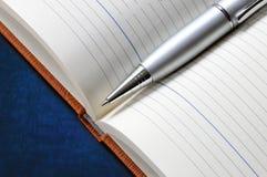 Silberner Metallstift auf dem geöffneten Notizbuch Nahaufnahme Stockbild