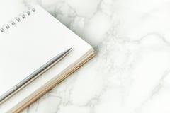 Silberner Metallstift auf leerer Notizbuchseite auf Marmorschreibtisch Stockfoto