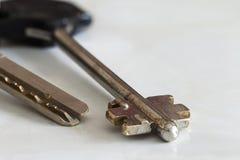 Silberner Schlüssel gegen weiße Hintergrundnahaufnahme Stockbild