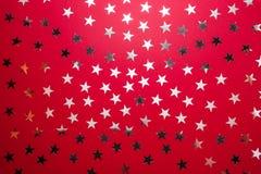 Silberner Stern besprüht auf rotem backgound Festliche Feiertagskonfettis Getrennt auf Weiß Draufsicht, flache Lage stockfotografie
