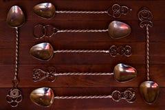 silberner Teelöffel vereinbart über dunklem Holztisch Stockfoto
