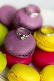 Silberner Verlobungsring und Eheringe auf Makronen Stockbild