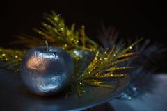 Silbernes Apple auf einer Untertasse in der Atmosphäre von Weihnachten Lizenzfreie Stockbilder