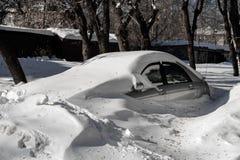 Silbernes Auto ist im Parkplatz in einer großen Schnee Bank Wetterprobleme Stockfotografie