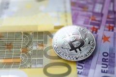 Silbernes bitcoin mit Eurobargeldlüge auf dem Tisch stockfotografie