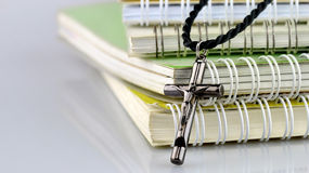 Silbernes christliches Kreuz auf Büchern Stockfoto