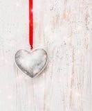 Silbernes Herz, das an der roten Schnur auf weißer hölzerner Wand, Liebe hängt Stockbilder