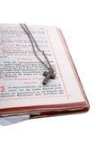 Silbernes Kreuz in einer geöffneten alten Bibel lizenzfreies stockfoto