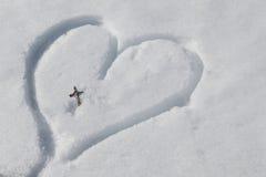 Silbernes Kruzifix auf dem Herzen gezeichnet in den Schnee lizenzfreie stockfotografie