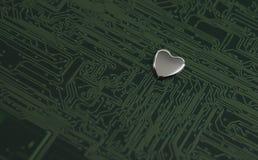Silbernes metallisches Herz in einem Grün färbte Leiterplatte Stockbilder